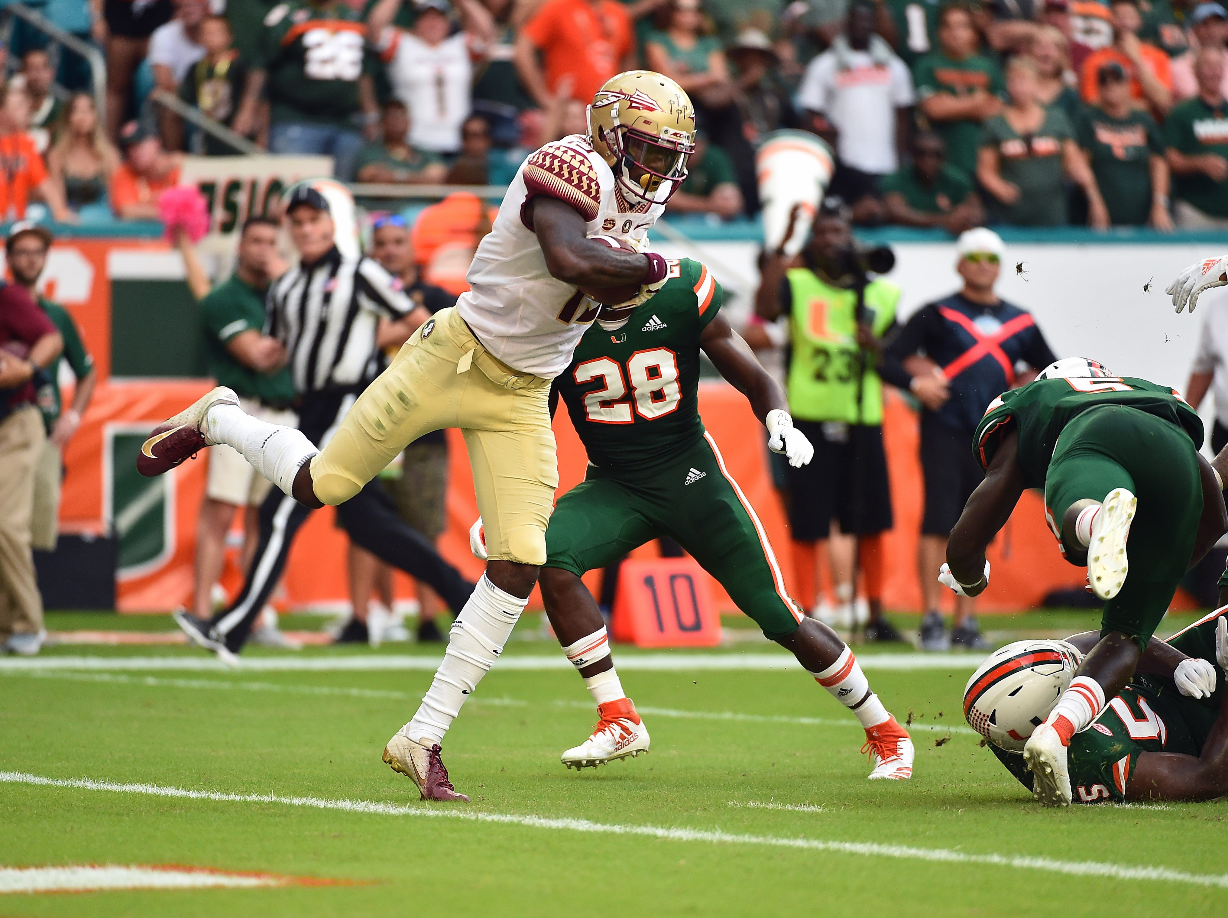 Oct 6, 2018; Miami Gardens, FL, USA; Florida State Seminoles quarterback Beau Fillichio (19) scores a touchdown against the Miami Hurricanes during the first half at Hard Rock Stadium. Mandatory Credit: Jasen Vinlove-USA TODAY Sports