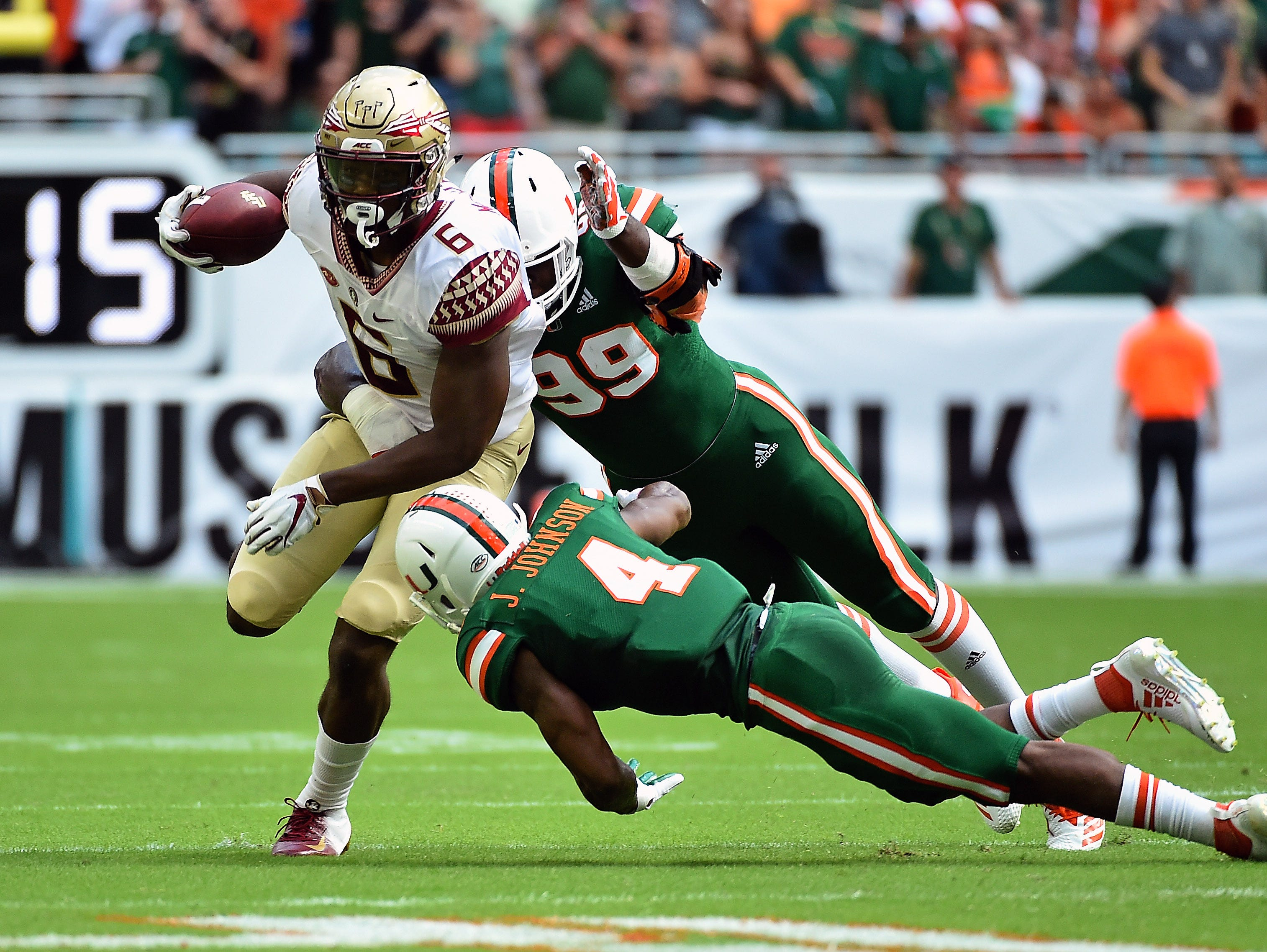 Oct 6, 2018; Miami Gardens, FL, USA; Miami Hurricanes defensive back Jaquan Johnson (4) and defensive lineman Joe Jackson (99) chase Florida State Seminoles tight end Tre' McKitty (6) during the first half at Hard Rock Stadium. Mandatory Credit: Jasen Vinlove-USA TODAY Sports