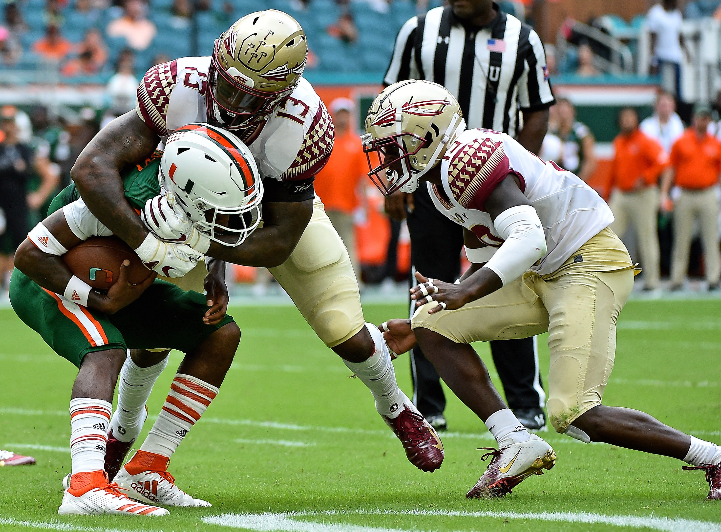 Oct 6, 2018; Miami Gardens, FL, USA; Florida State Seminoles defensive end Joshua Kaindoh (13) tackles Miami Hurricanes quarterback N'Kosi Perry (5) during the first half at Hard Rock Stadium. Mandatory Credit: Jasen Vinlove-USA TODAY Sports