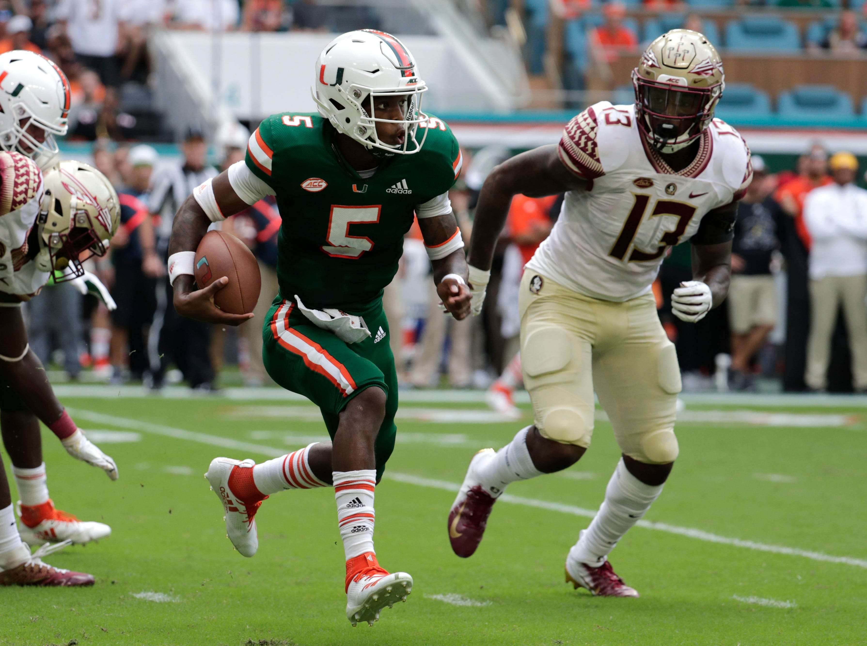 Miami quarterback N'Kosi Perry (5) runs as Florida State defensive end Joshua Kaindoh (13) defends during the first half of an NCAA college football game, Saturday, Oct. 6, 2018, in Miami Gardens, Fla. (AP Photo/Lynne Sladky)
