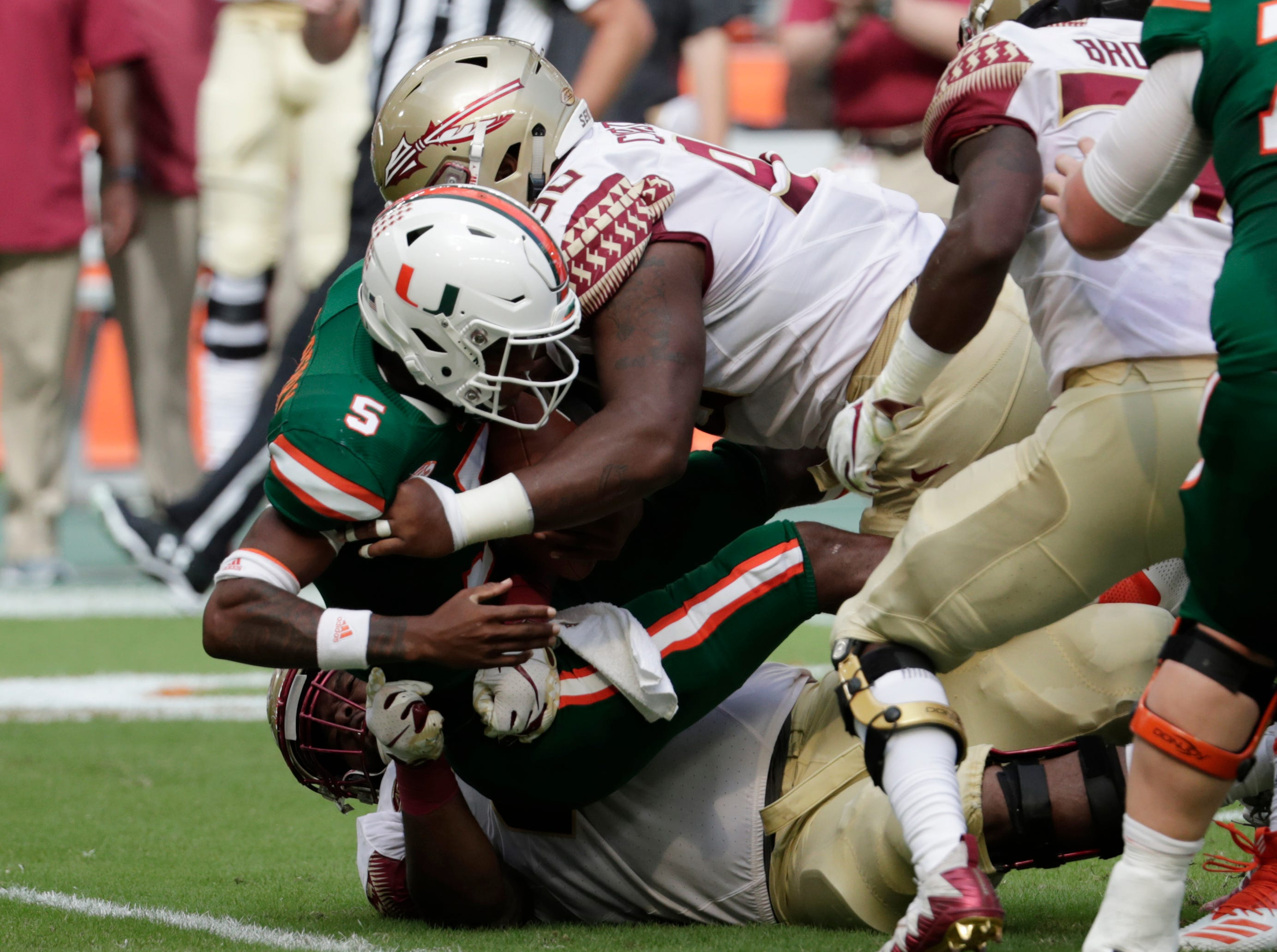 Miami quarterback N'Kosi Perry (5) is sacked by Florida State defensive tackle Demarcus Christmas (90) during the first half of an NCAA college football game, Saturday, Oct. 6, 2018, in Miami Gardens, Fla. (AP Photo/Lynne Sladky)