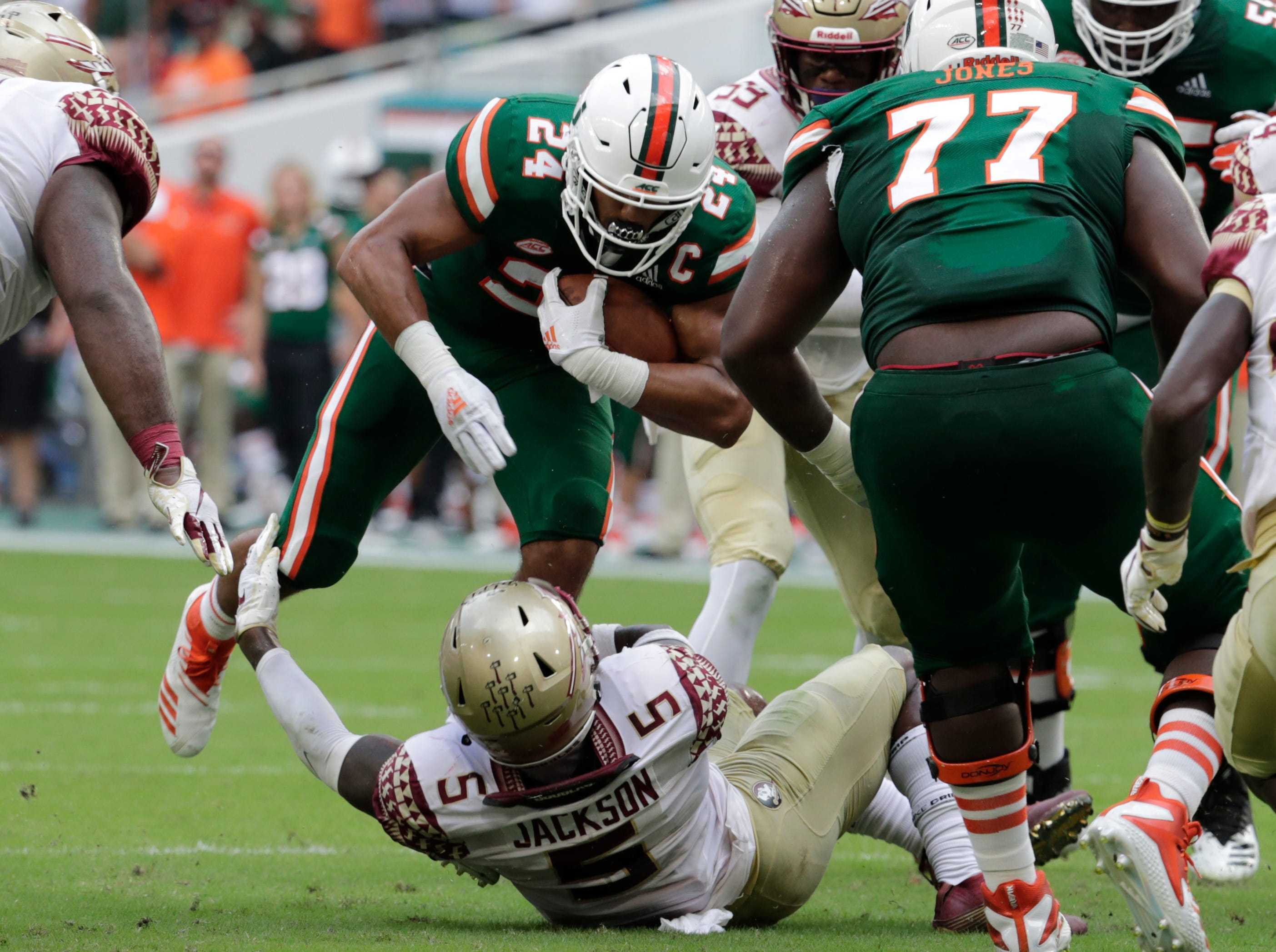 Miami running back Travis Homer (24) runs as Florida State linebacker Dontavious Jackson (5) defends during the first half of an NCAA college football game, Saturday, Oct. 6, 2018, in Miami Gardens, Fla. (AP Photo/Lynne Sladky)