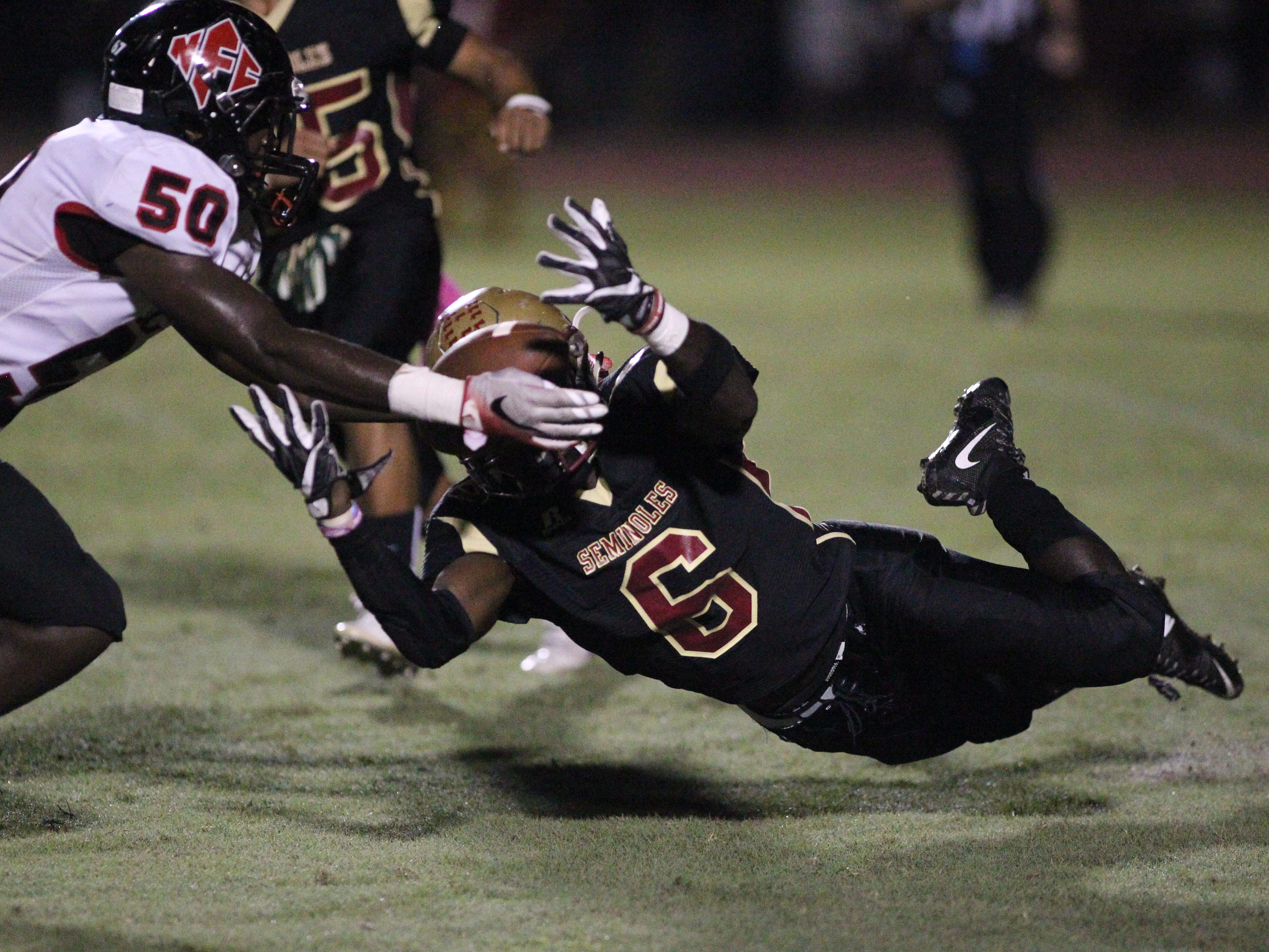 NFC's Raymond Jackson hits Florida High's Alfred Menjor before Menjor can recover a fumble, leading to a turnover.
