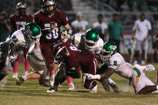 Chiles running back Jalen Herring tries to pick up hard yards as Suwannee defenders grab hold.