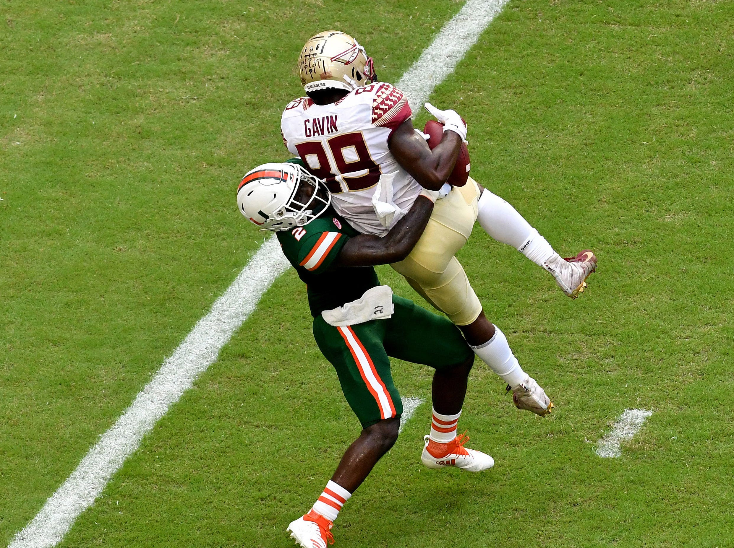 Oct 6, 2018; Miami Gardens, FL, USA; Florida State Seminoles wide receiver Keith Gavin (89) catches a touch down catch as Miami Hurricanes defensive back Trajan Bandy (2) makes the tackle during the first half at Hard Rock Stadium. Mandatory Credit: Steve Mitchell-USA TODAY Sports