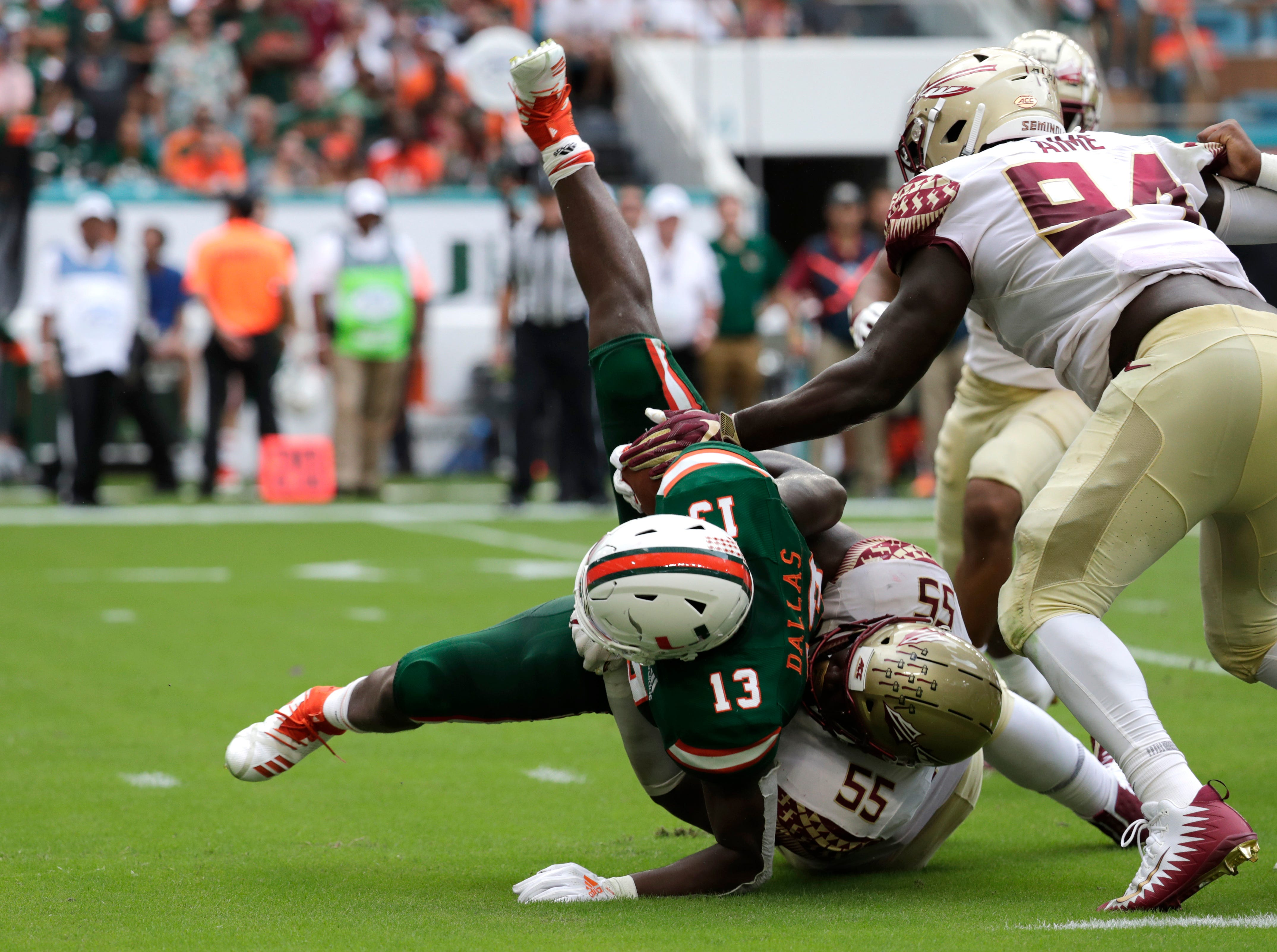 Miami running back DeeJay Dallas (13) is tackled by Florida State defensive tackle Fredrick Jones (55) during the first half of an NCAA college football game, Saturday, Oct. 6, 2018, in Miami Gardens, Fla. (AP Photo/Lynne Sladky)