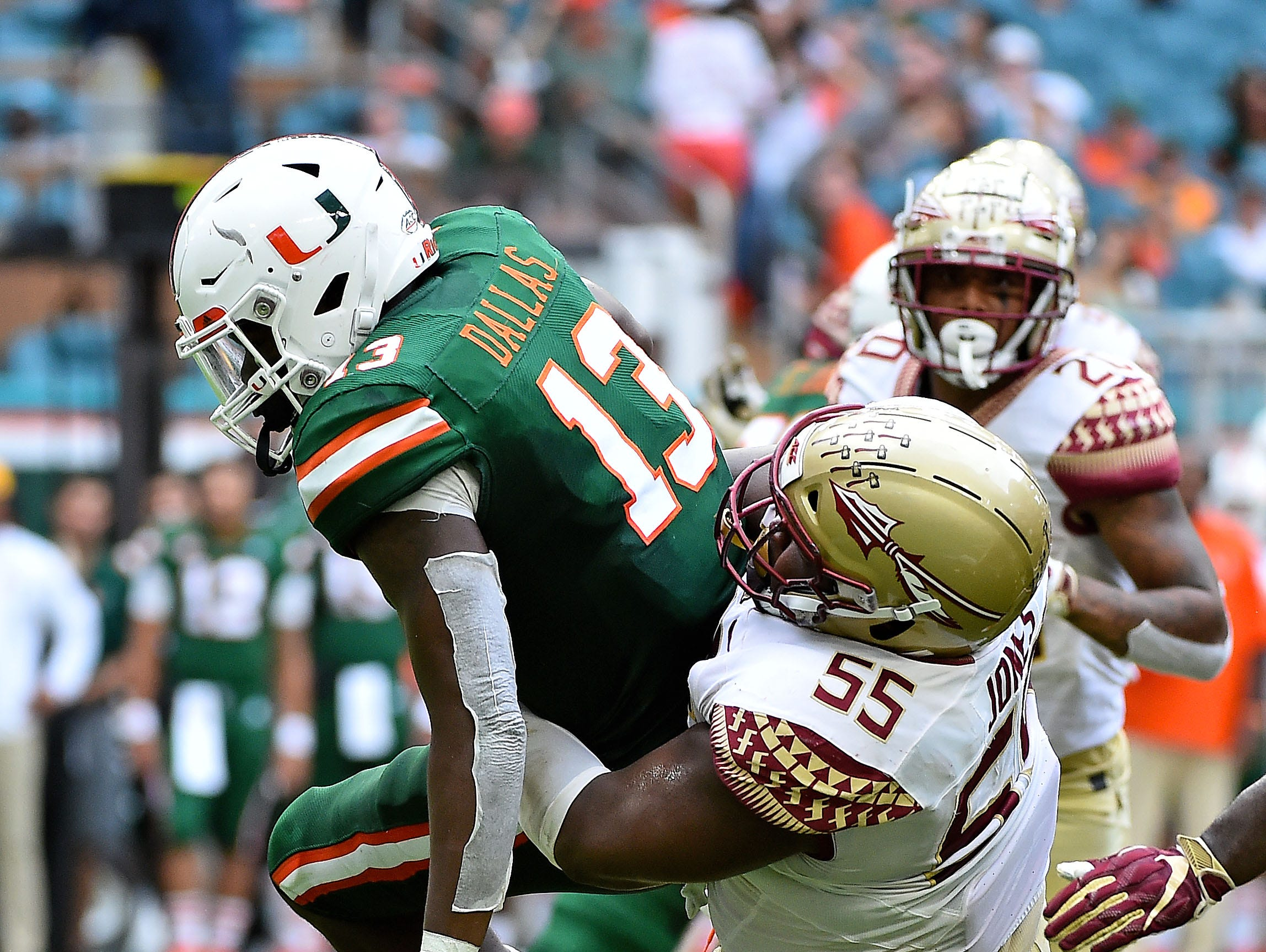Oct 6, 2018; Miami Gardens, FL, USA; Florida State Seminoles defensive tackle Fredrick Jones (55) tackles Miami Hurricanes running back DeeJay Dallas (13) during the first half at Hard Rock Stadium. Mandatory Credit: Jasen Vinlove-USA TODAY Sports