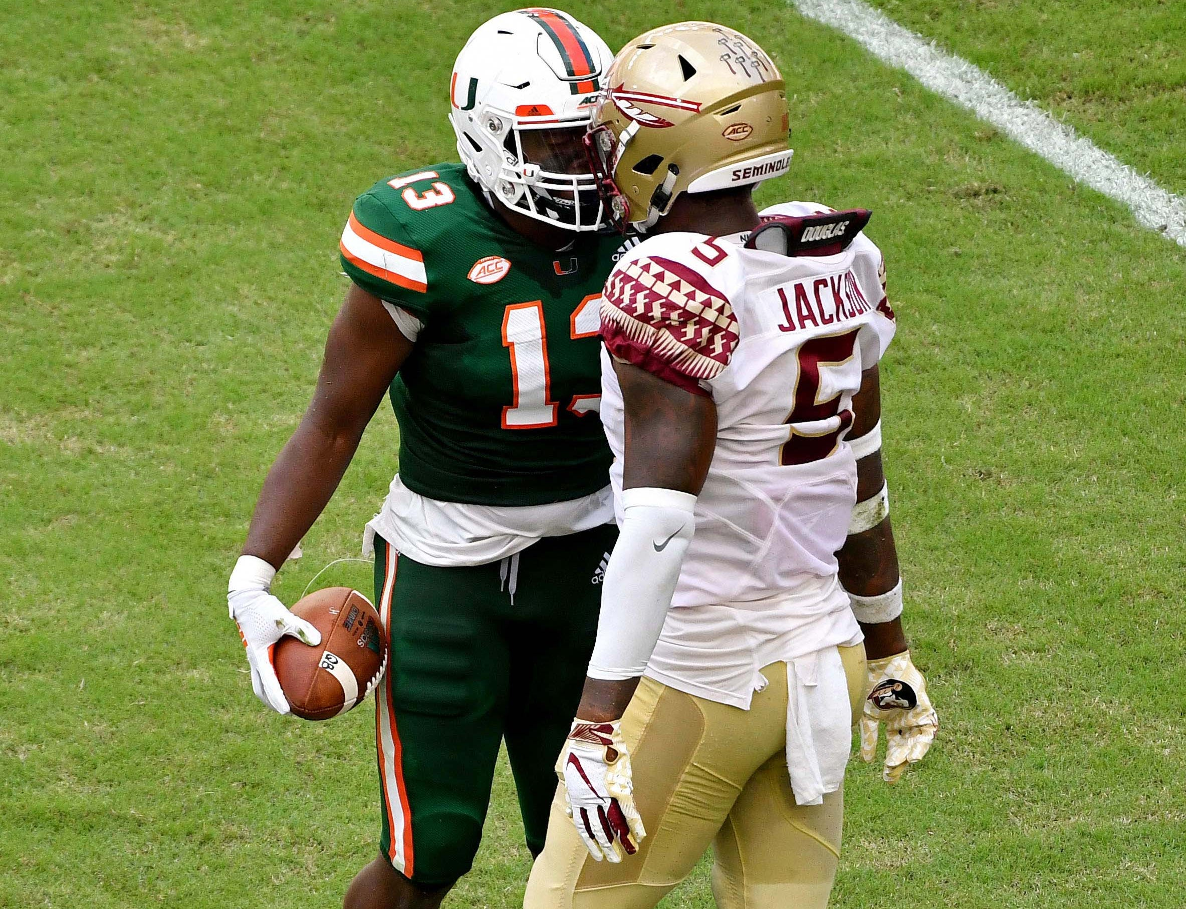 Oct 6, 2018; Miami Gardens, FL, USA; Miami Hurricanes running back DeeJay Dallas (13) and Florida State Seminoles linebacker Dontavious Jackson (5) both exchange words during the first half at Hard Rock Stadium. Mandatory Credit: Steve Mitchell-USA TODAY Sports