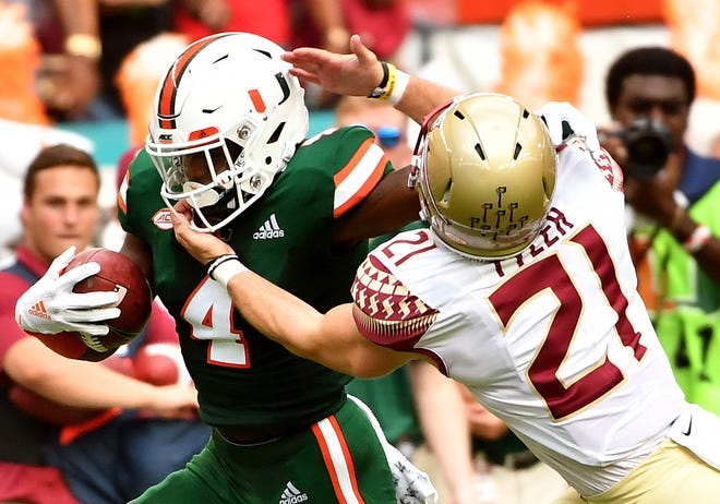 Oct 6, 2018; Miami Gardens, FL, USA; Florida State Seminoles punter Logan Tyler (21) pulls on the facemask of Miami Hurricanes wide receiver Jeff Thomas (4) during the first half at Hard Rock Stadium. Mandatory Credit: Steve Mitchell-USA TODAY Sports