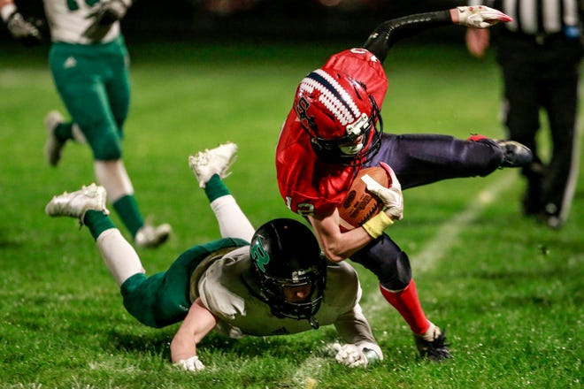 Spencer/Columbus' Austin Bacon(12), right, gets knock out by Regis' Tristan Root(9) Friday, Oct. 05, 2018, at Spencer High School football field in Spencer,