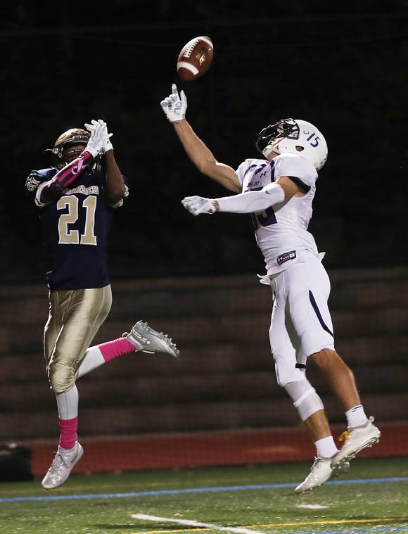 John Jay (CR) Luke Mercer (15) breaks up a pass intended for Lourdes' Kyle Strack (21) during football action at Our Lady of Lourdes High School Oct. 5, 2018.