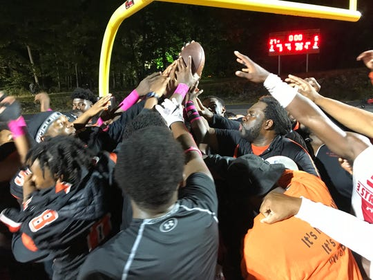 Spring Valley football head coach Andrew Delva (center) celebrates with his team after defeating Byram Hills, 27-6, to secure a playoff spot. Oct. 5, 2018.