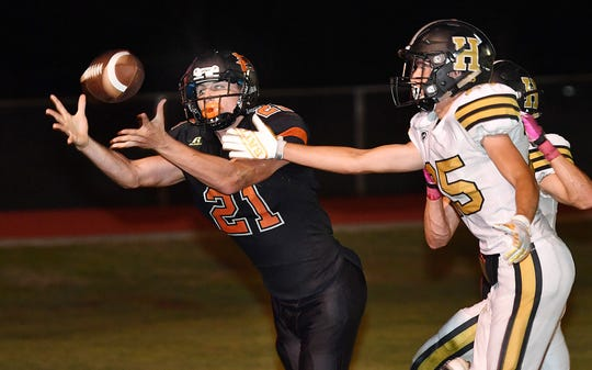 Nocona tight end Jason Sparkman (21) catches a second quarter touchdown pass in front of Henrietta's Brandon Lee (25) Friday night in Nocona.