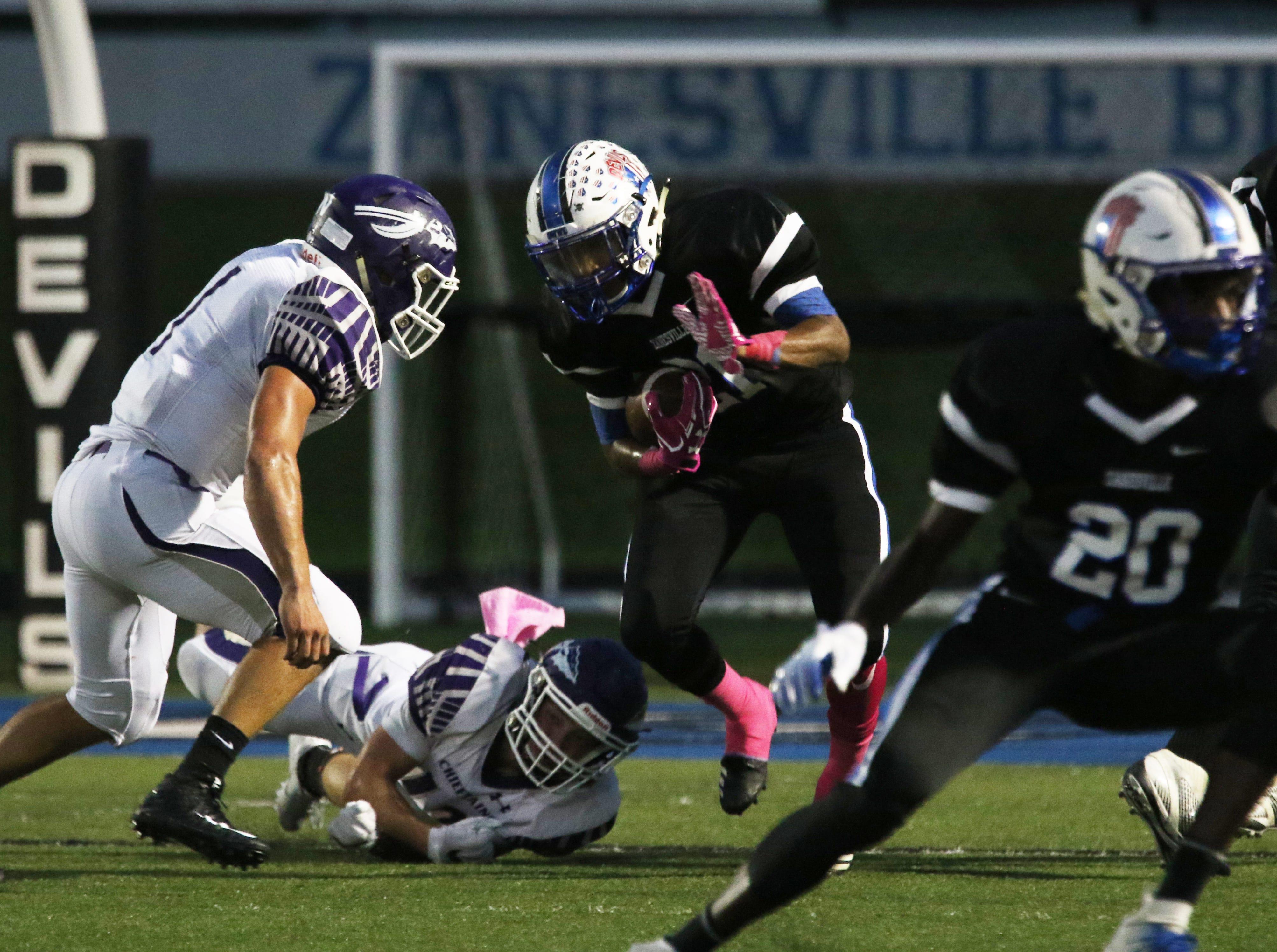 Zanesville's Julius Murphy fights for yards against Logan.