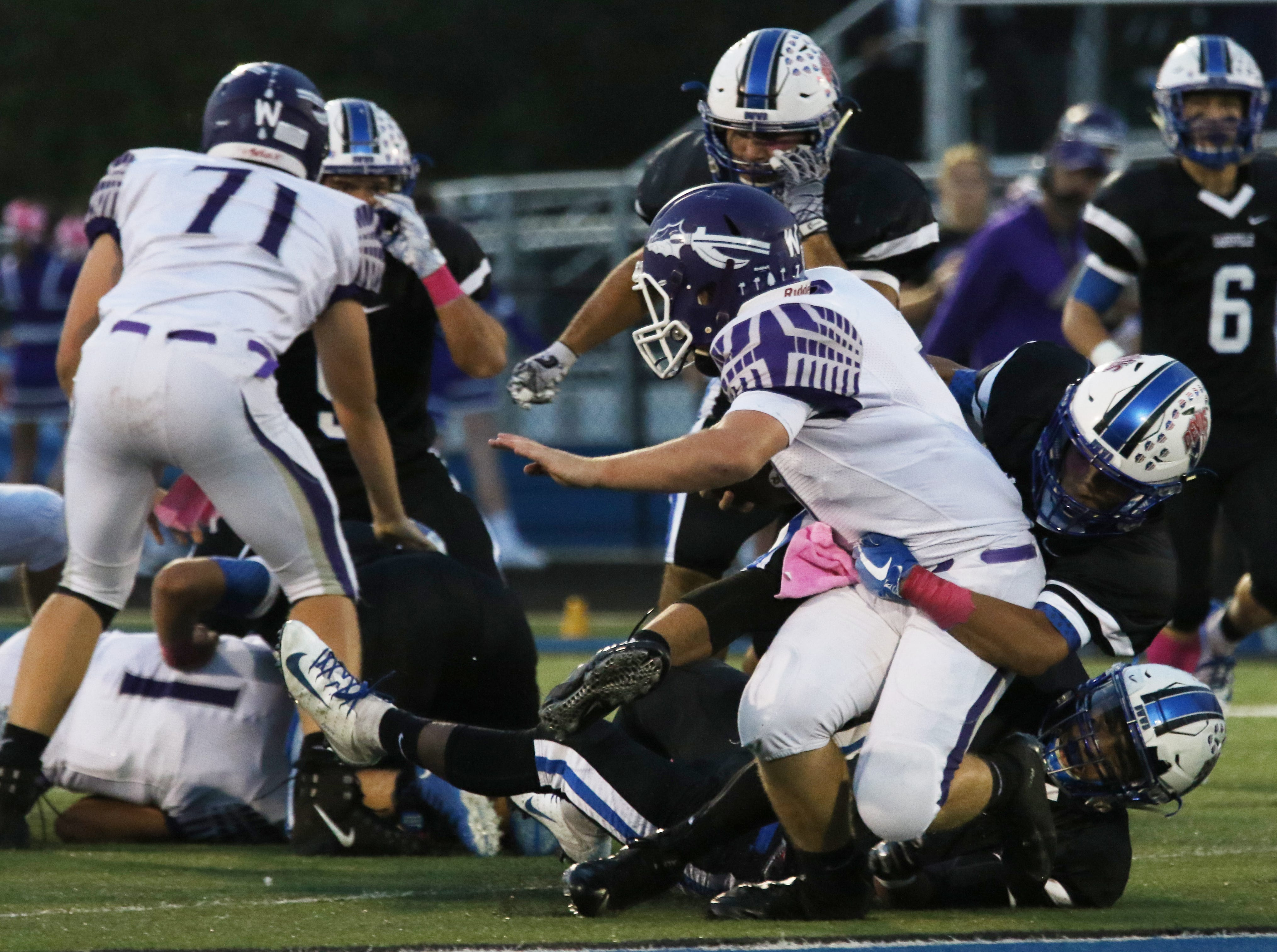 A pair of Zanesville defenders take down a Logan ball carrier.