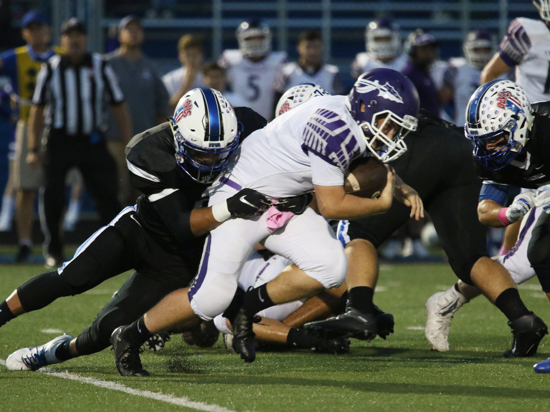 A Zanesville defender pulls down a Logan ball carrier.