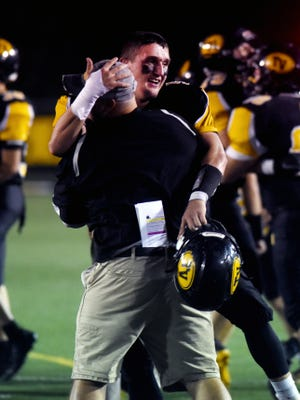 Tri-Valley senior linebacker Kaden Lawler hugs an assistant coach following the Scotties' 20-19 overtime win against Sheridan on Friday night at Jack Anderson Stadium.