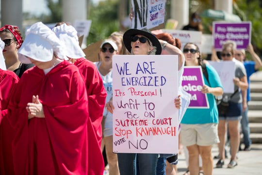 People march in downtown Fort Lauderdale, Fla., against Brett Kavanaugh's nomination to the Supreme Court on Saturday, Oct. 6, 2018.