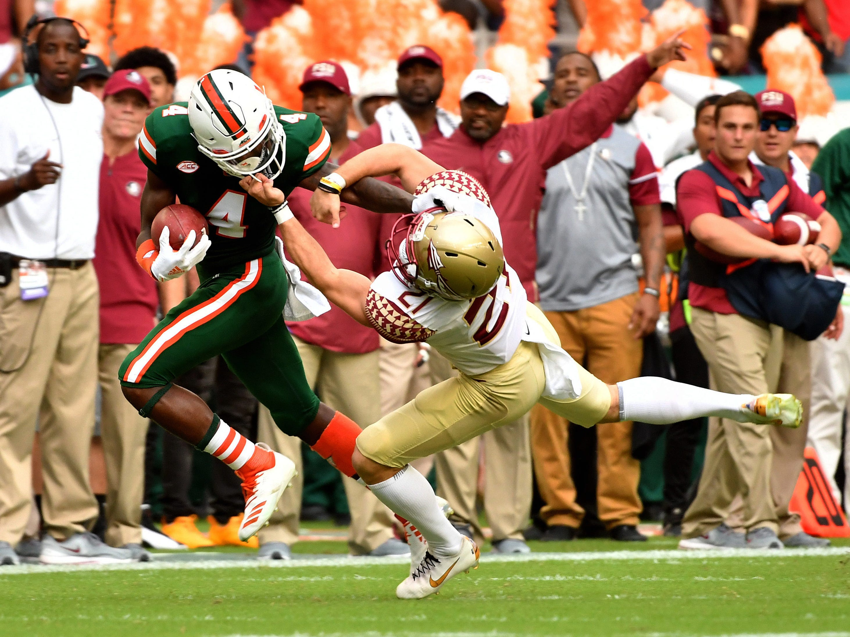 Florida State Seminoles punter Logan Tyler pulls on the facemask of Miami Hurricanes wide receiver Jeff Thomas during the first half at Hard Rock Stadium.