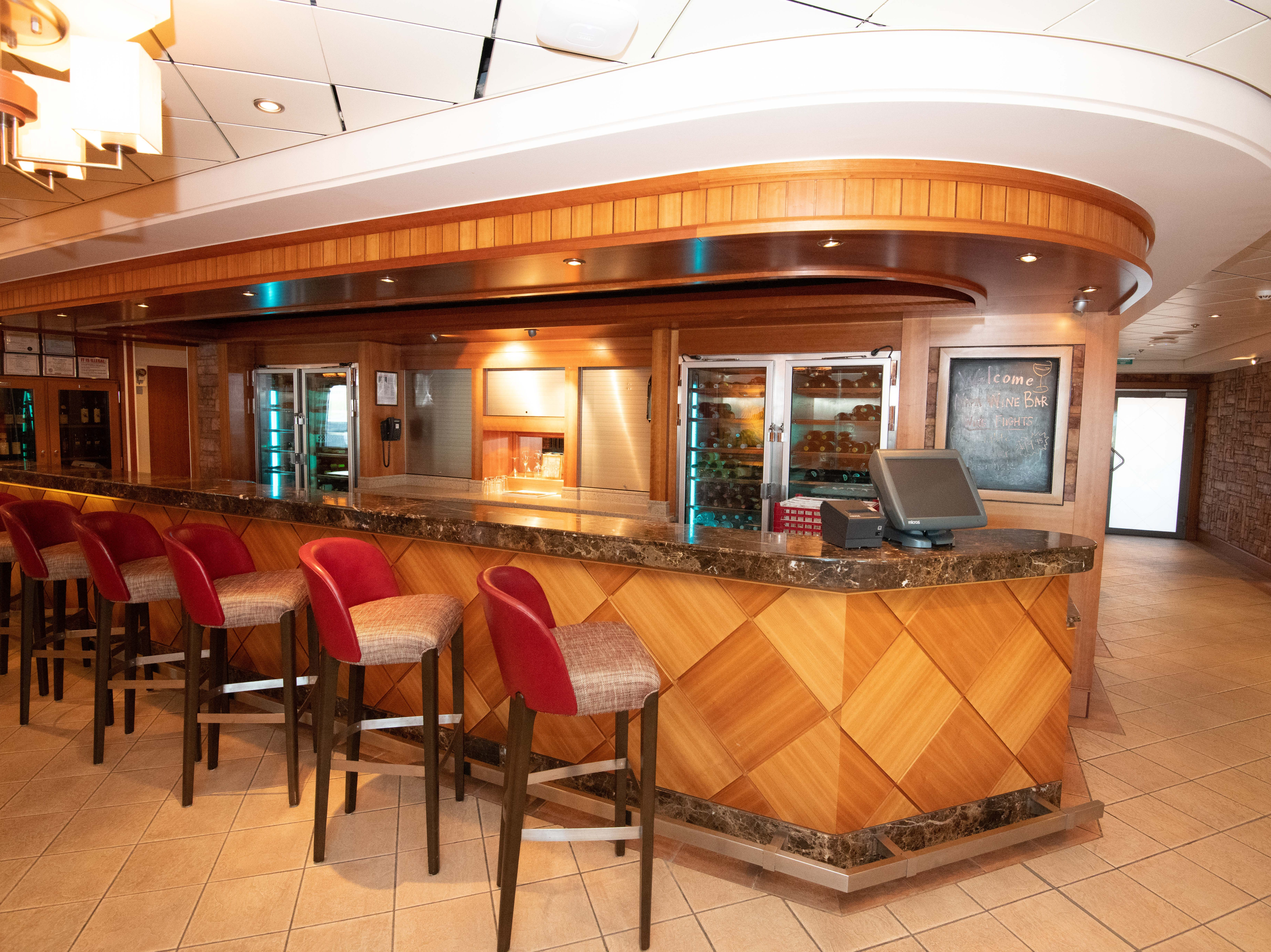 The granite-topped bar at the center of Pride of America's Napa Wine Bar is a popular spot for pre-dinner drinks.