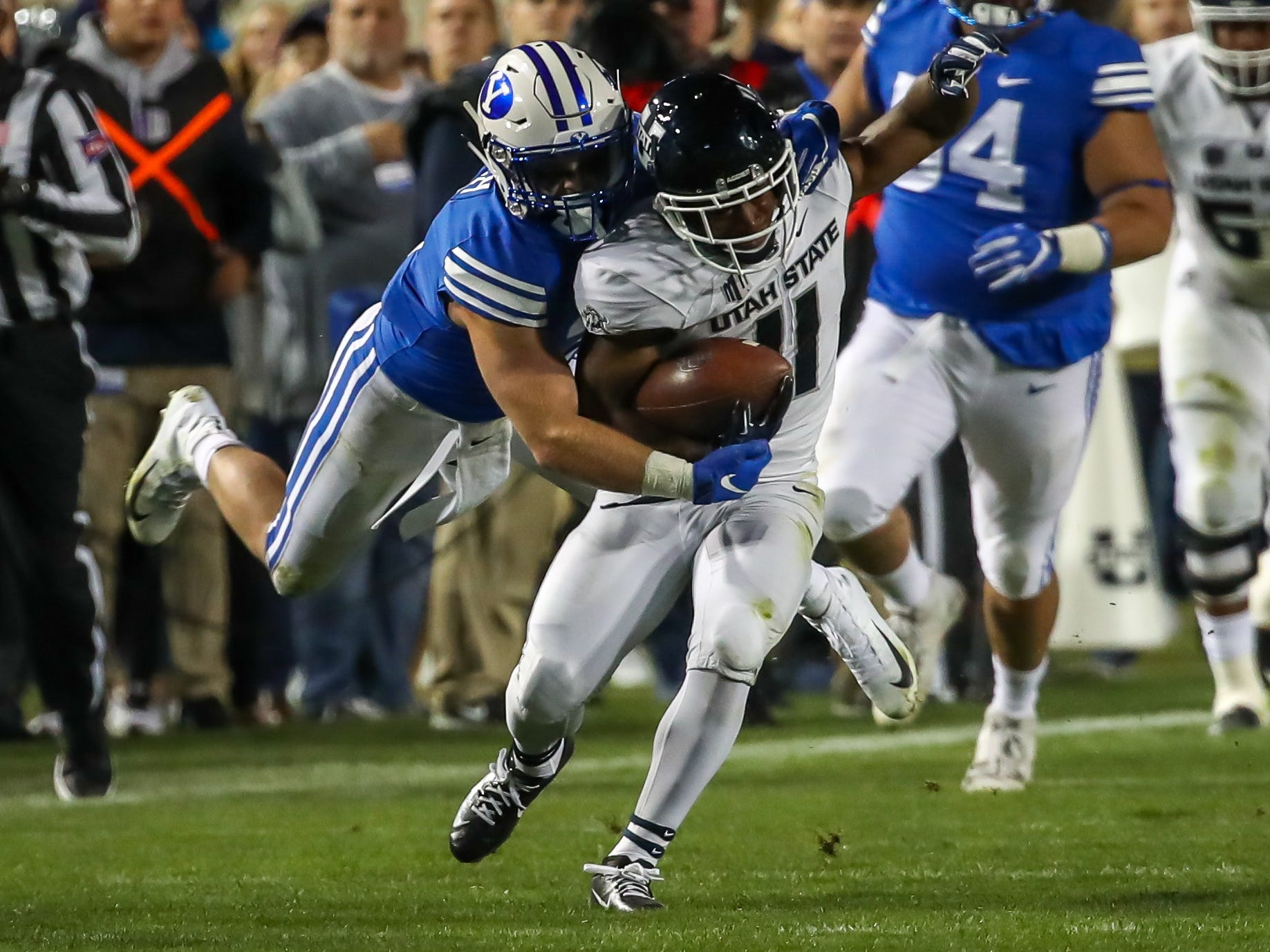 Utah State receiver Aaren Vaughns (11) tries to elude a BYU defender after a second-half catch.
