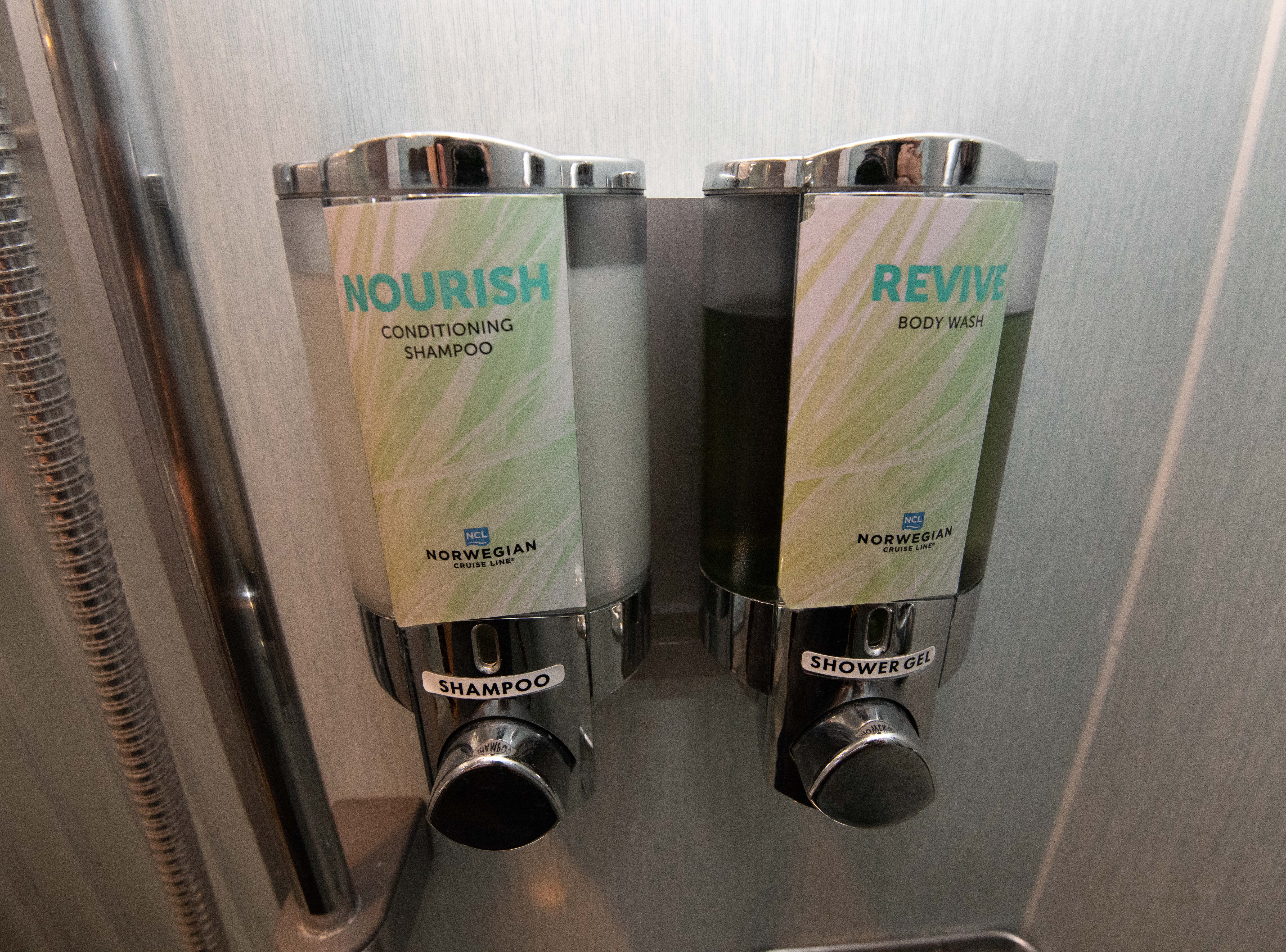 Large dispensers in the showers in Pride of America cabins are filled with body wash and shampoo.