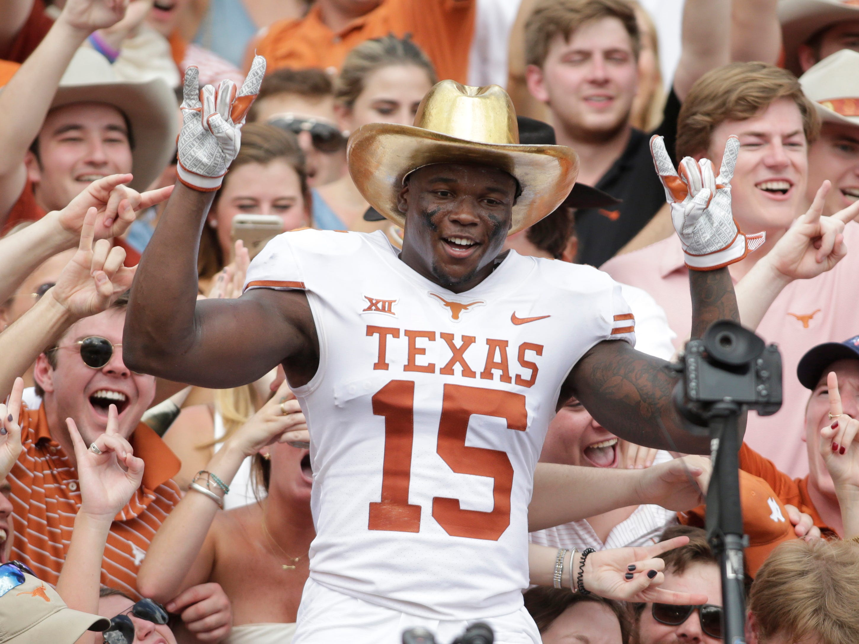 Texas Longhorns defensive back Chris Brown celebrates in the crowd with the Golden Hat after a game against the Oklahoma Sooners at the Cotton Bowl.