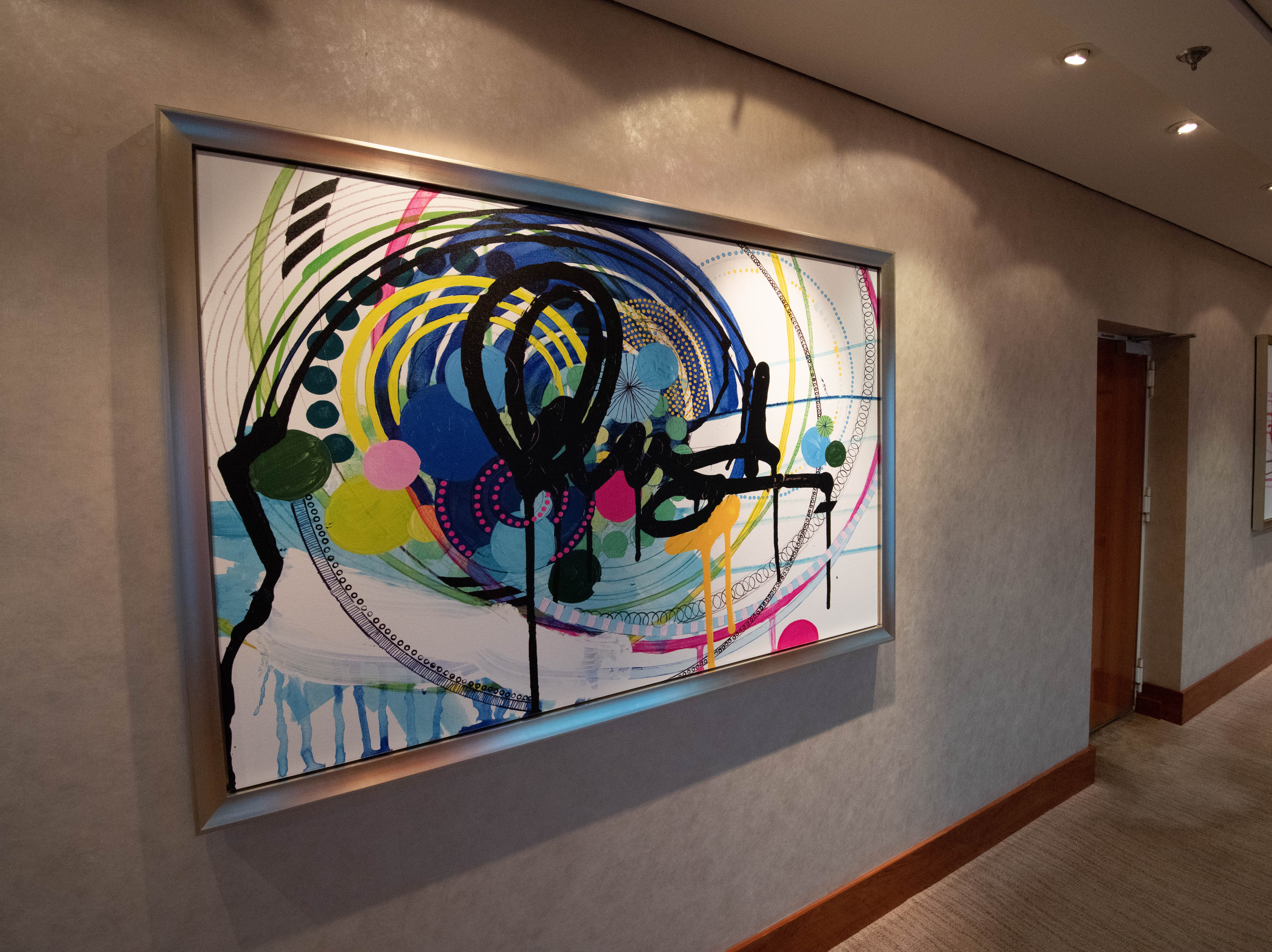 Contemporary art lines the hallway between the Skyline Main Dining Room and Capitol Atrium on Deck 5.