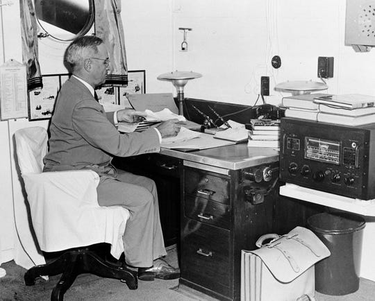 In this Aug. 6, 1945, file photo, aboard the cruiser Augusta, President Harry S. Truman, with a radio at hand, reads reports of the first atomic bomb raid on Japan, while en route home from the Potsdam conference.