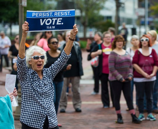 Jane Pitz holds up a sign during the We Believe Them rally, Saturday, Oct. 6, 2018, in downtown South Bend, Ind.