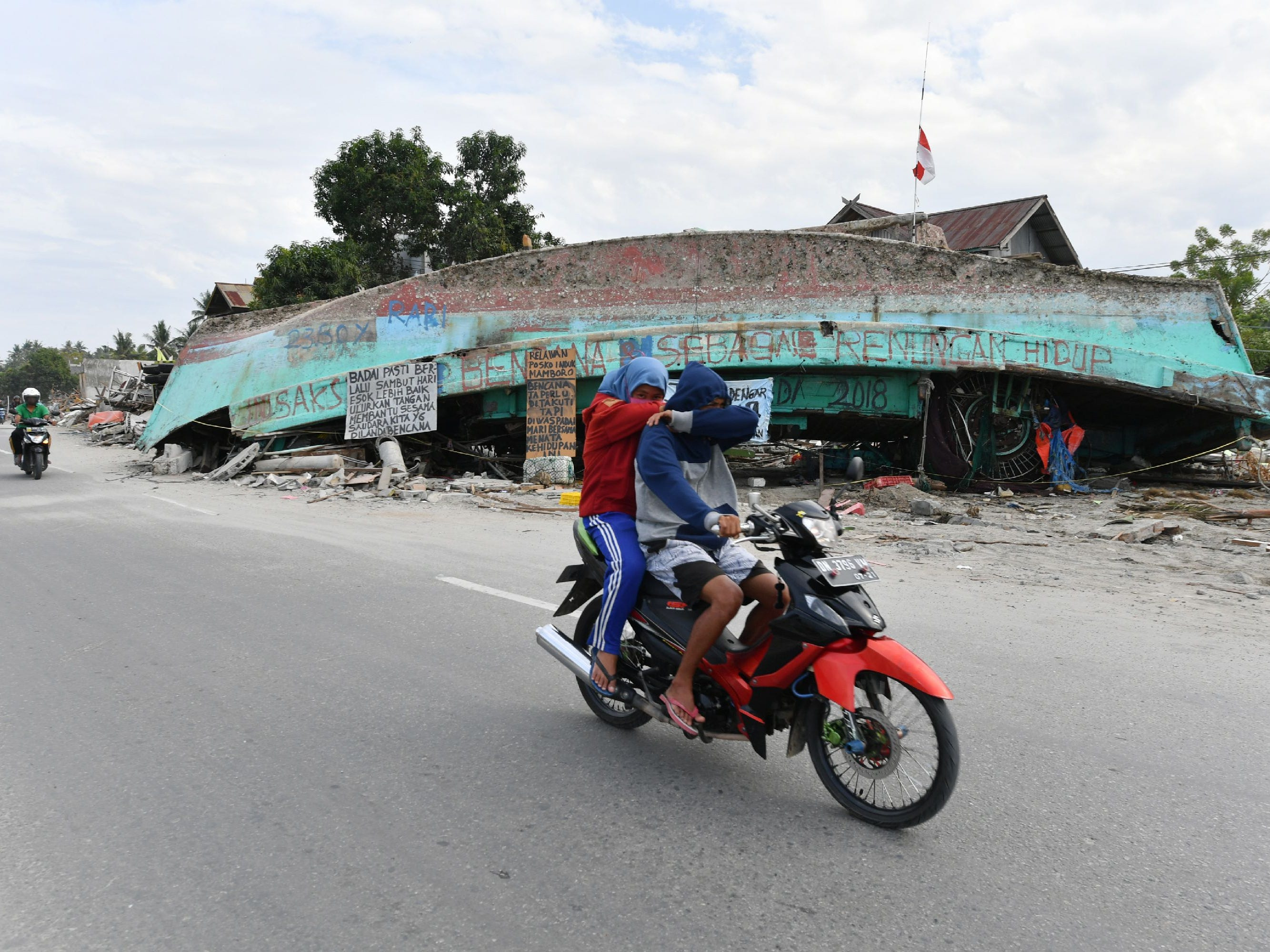 Motorists drive past an upside down boat in Mamboro, Indonesia's Central Sulawesi on Oct. 6, 2018, following the Sept. 28 earthquake and tsunami.