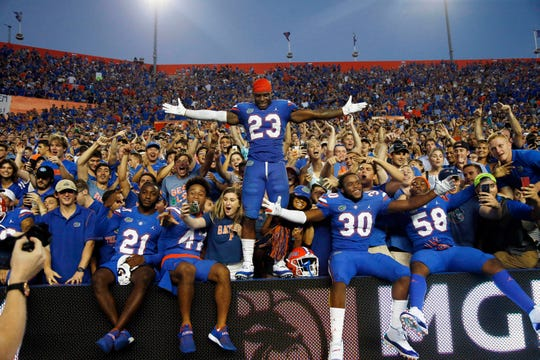Florida Gators defensive back Chauncey Gardner-Johnson, safety Amari Burney and teammates celebrate with fans as they beat LSU in 2018 at Ben Hill Griffin Stadium.