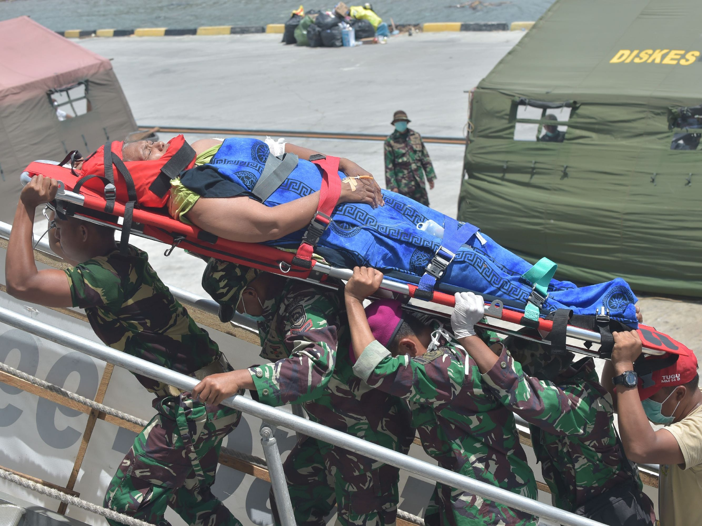 Indonesian marines carry a patient into the floating hospital KRI Soeharso operated by the Indonesian navy in Pantoloan , Indonesia's Central Sulawesi on Oct. 6, 2018.