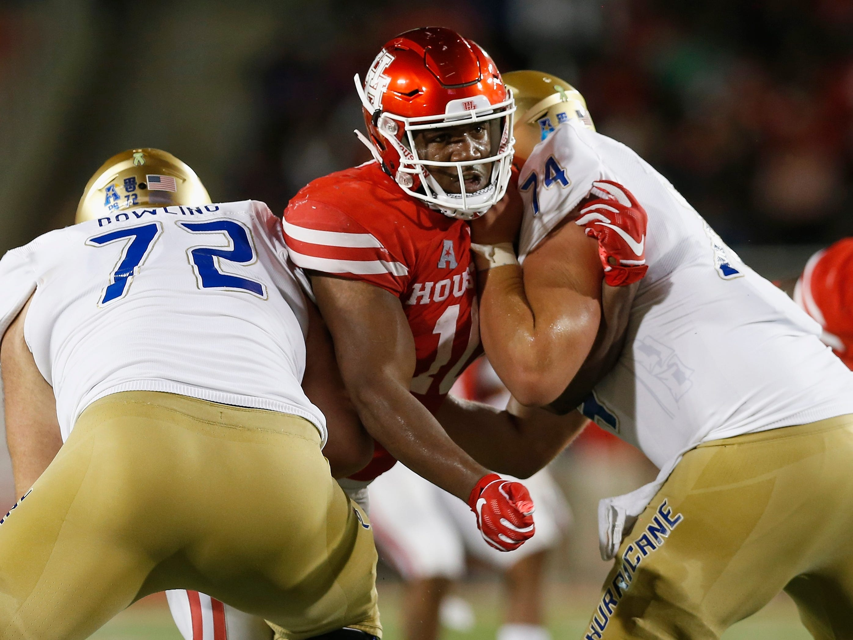 Houston defender Ed Oliver (10) tries to fight through the double-team by Tulsa linemen Tyler Bowling (72) and Chandler Miller (74) during the first half.