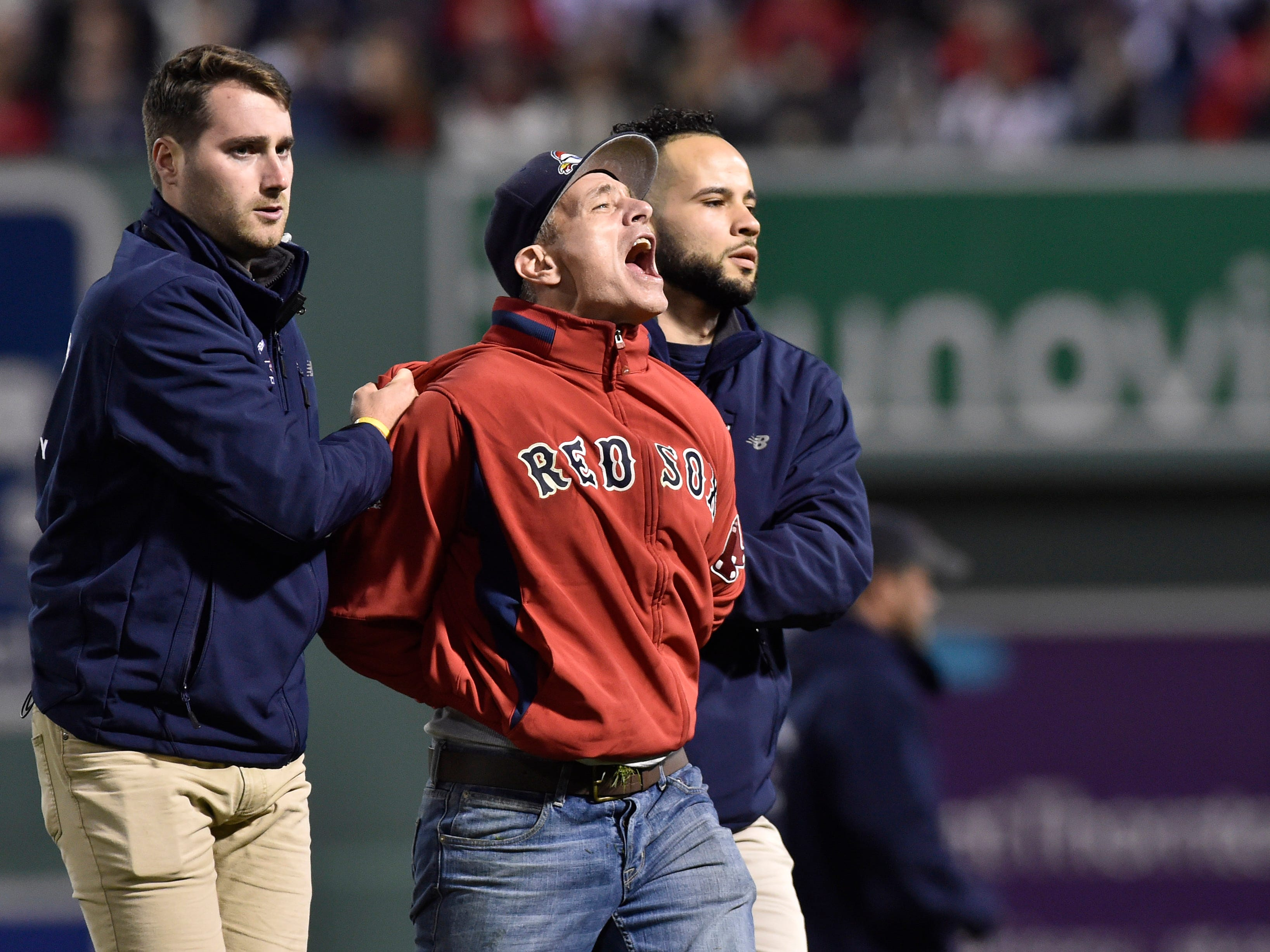 ALDS Game 1: A Red Sox fan is escorted after running on the field in the fifth inning.