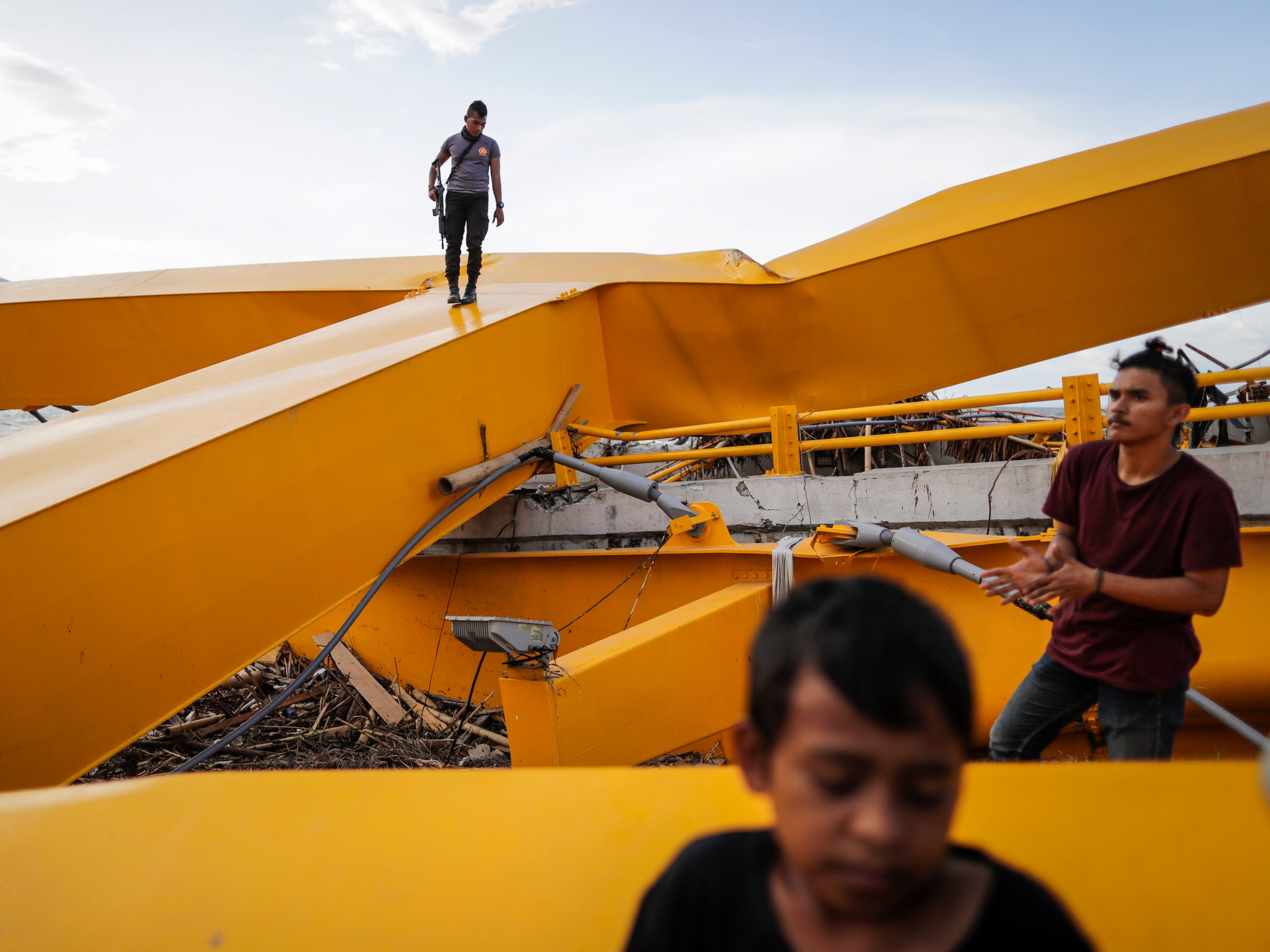People inspect the 'Palu Empat' bridge that was destroyed during a tsunami at Talise beach in Palu, Central Sulawesi, Indonesia, Oct. 6, 2018.