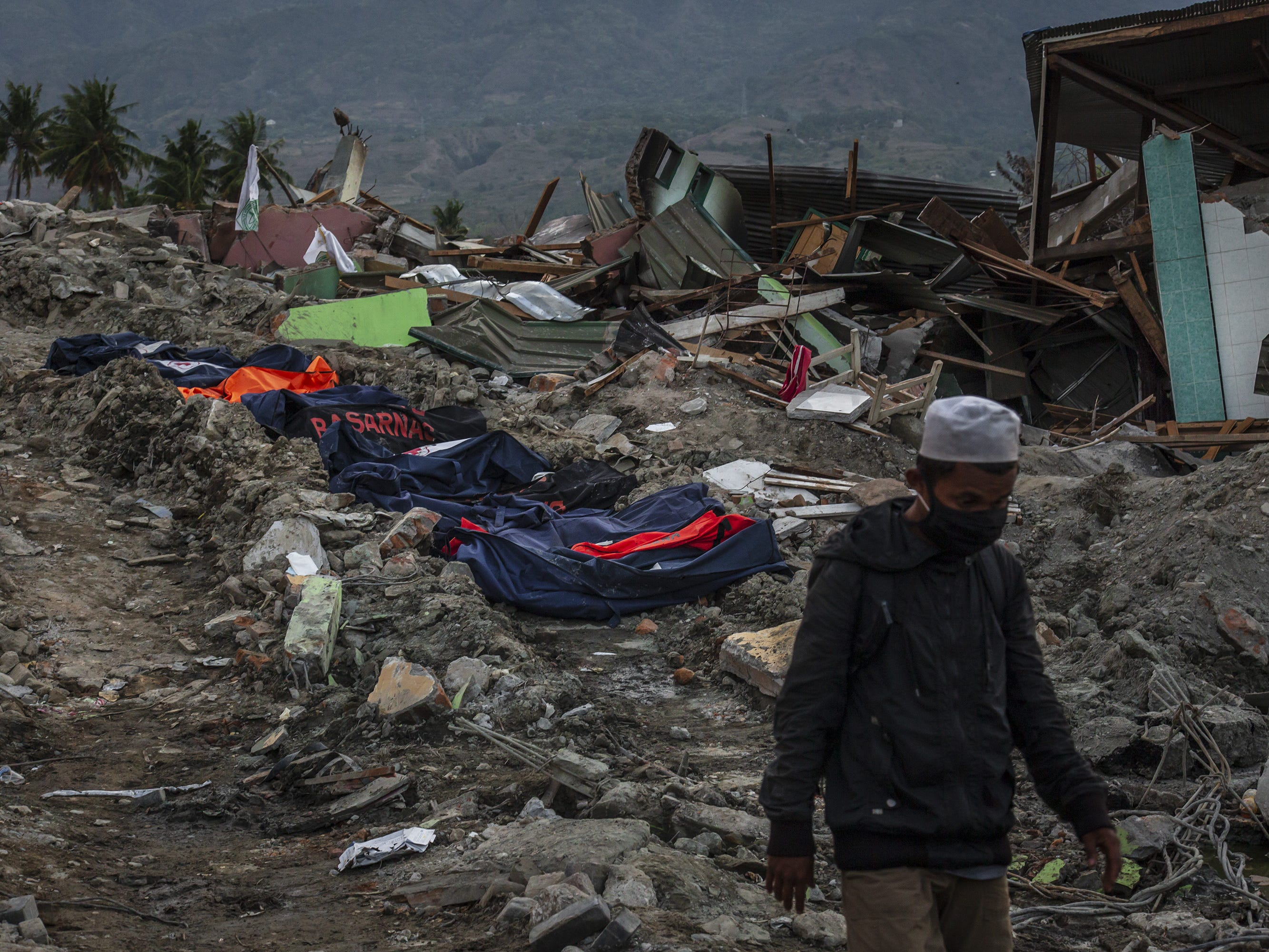 An Indonesian man walks past bodies of victims at Balaroa village following an earthquake, Oct. 6, 2018, in Palu, Central Sulawesi, Indonesia. The death toll from last weeks earthquake and tsunami has risen to more than 1,500, but power had returned to parts of the city and fuel shipments have begun.