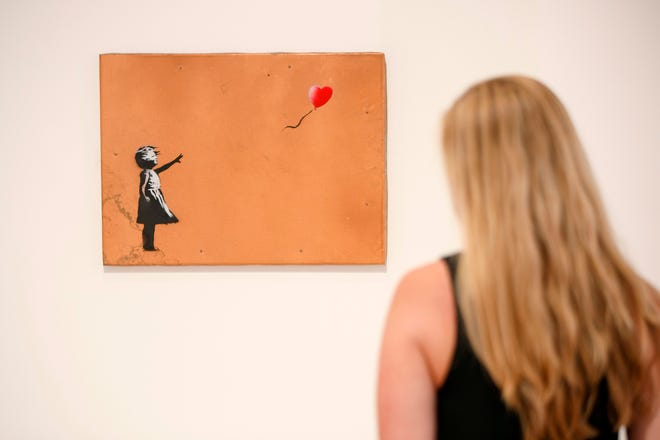 A gallery assistant poses with 'Girl with Balloon' 2006 artwork by Banksy at Lazinc Gallery in London on July 11, 2018.