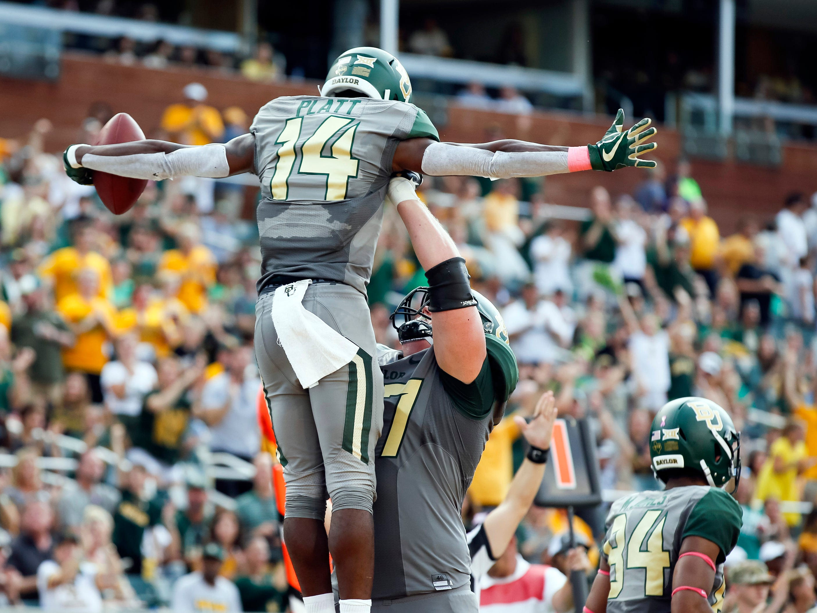 Baylor Bears wide receiver Chris Platt is lifted in the air by offensive lineman Patrick Lawrence after converting on a two-point conversion against the Kansas State Wildcats during the second half at McLane Stadium.