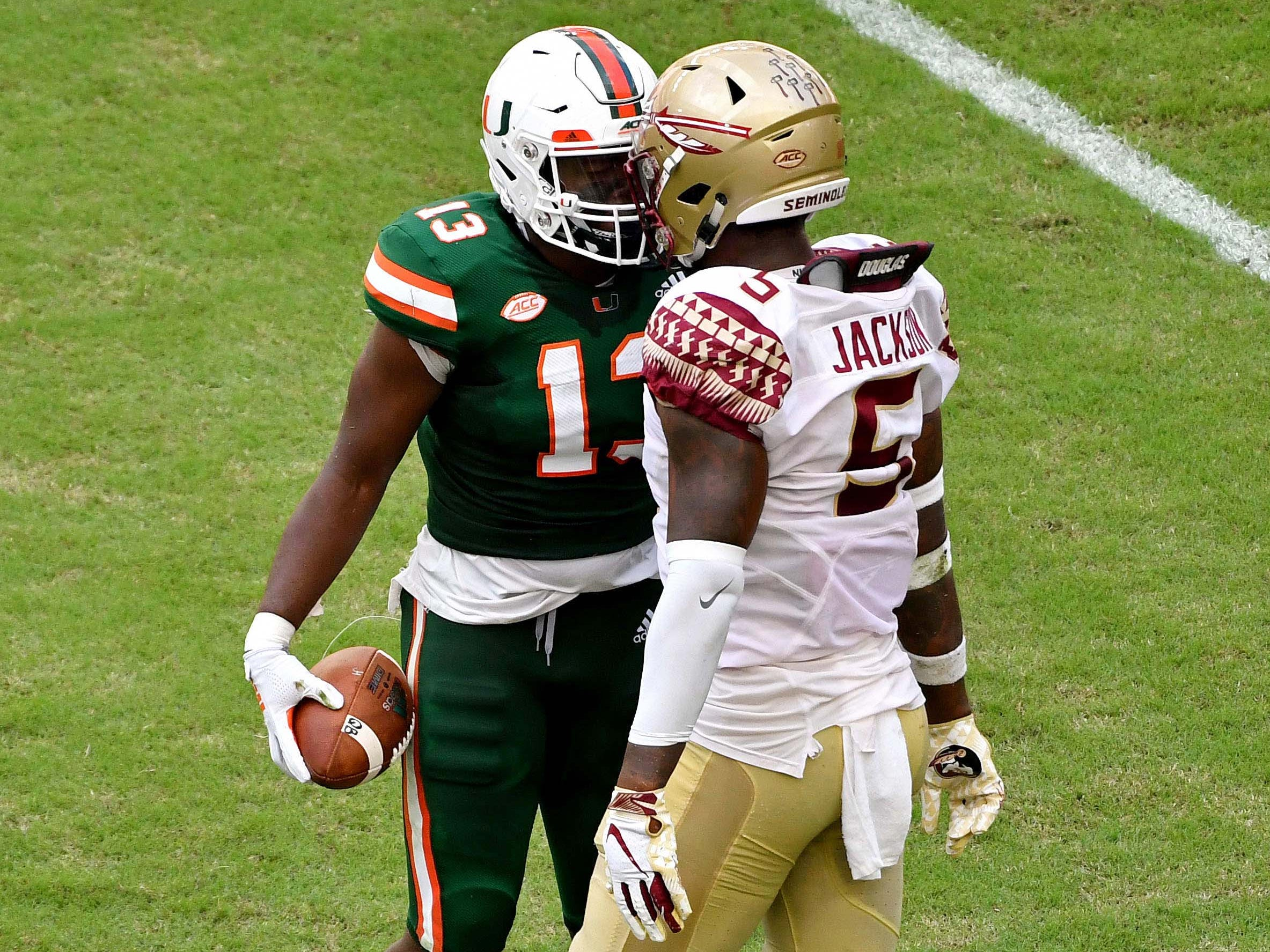 Miami Hurricanes running back DeeJay Dallas and Florida State Seminoles linebacker Dontavious Jackson both exchange words during the first half at Hard Rock Stadium.