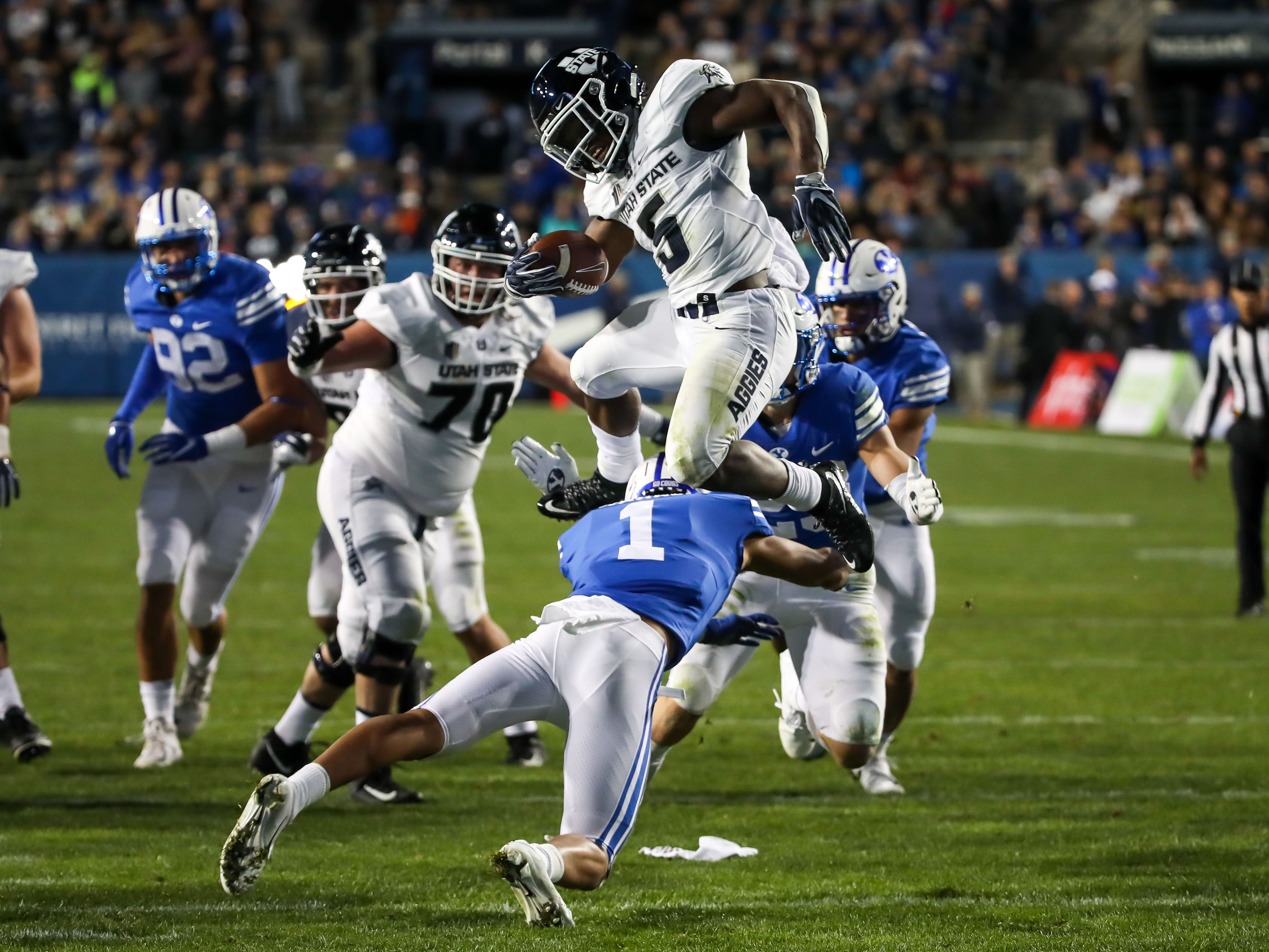 Utah State running back Darwin Thompson (5) tries to leap over BYU defender Troy Warner (1) on a second-half carry.