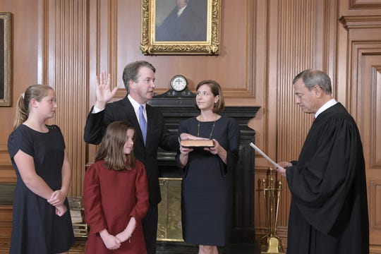 Chief Justice John G. Roberts Jr. administers the Constitutional Oath to Judge Brett M. Kavanaugh in the Justices' Conference Room at the Supreme Court Building on Oct. 6, 2018, in Washington. Kavanaugh wife, Ashley, holds the Bible. In the foreground are their daughters, Margaret, left, and Liza.