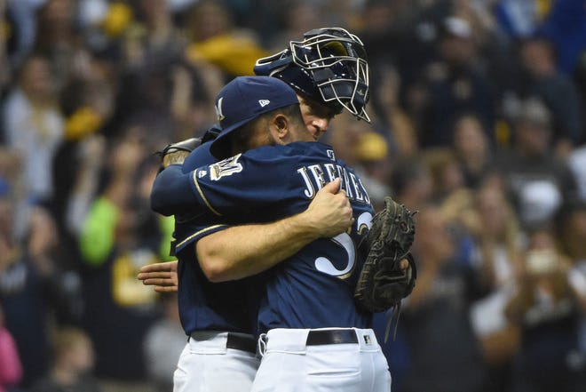 Milwaukee's Erik Kratz and relief pitcher Jeremy Jeffress celebrate after defeating Colorado in Game 2 of their NLDS.