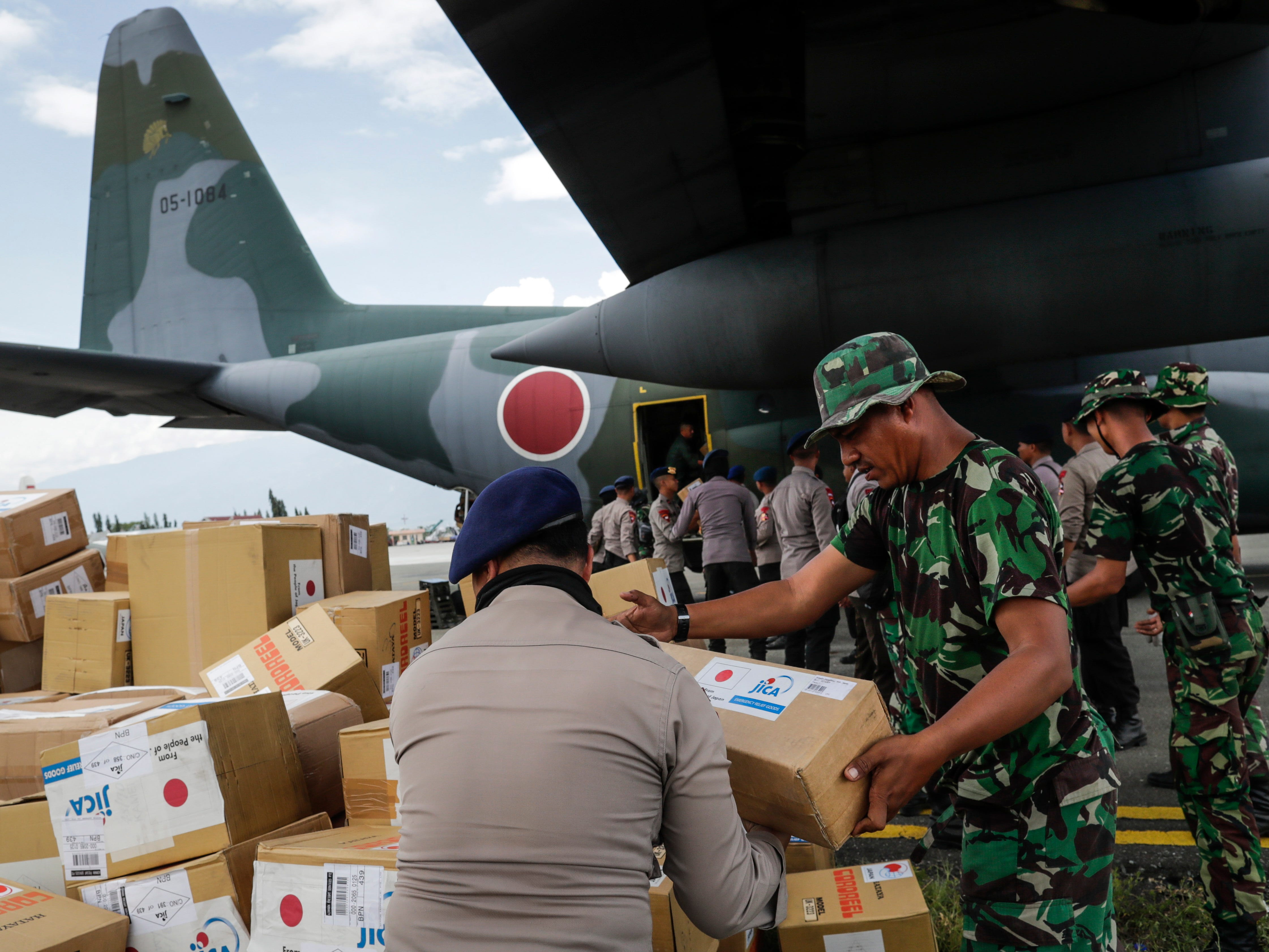 Members of the Japanese and Indonesian military unload humanitarian aid from a Japanese aircraft at the airport in Palu, Central Sulawesi, Indonesia, Oct. 6, 2018.