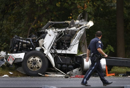 A police officer gazes at the damage to the cab of an oil tanker involved in an apparent fatal crash on Route 18 in Colts Neck on Saturday, Oct. 6, 2018.