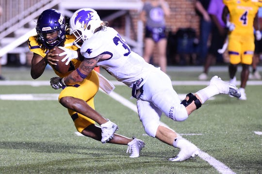 Hardin-Simmons linebacker Chris Miller (35) sacks UMHB's DeNerian Thomas (12) at Crusader Stadium in Belton on Saturday, Oct. 6, 2018.