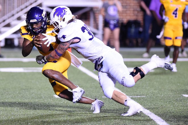 Hardin-Simmons linebacker Chris Miller (35) sacks UMHB's DeNerian Thomas (12) at Crusader Stadium in Belton on Saturday. The Cowboys defense held the Crusaders well under their season point average but the offense did not score in a 26-0 American Southwest Conference loss.