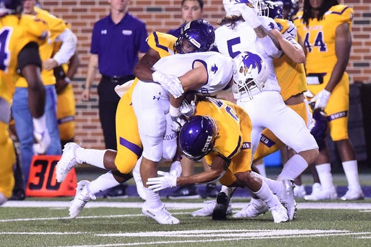 Hardin-Simmons receiver Bryson Hammonds (14) gets tackled between a pair of defenders against UMHB at Crusader Stadium in Belton on Saturday.
