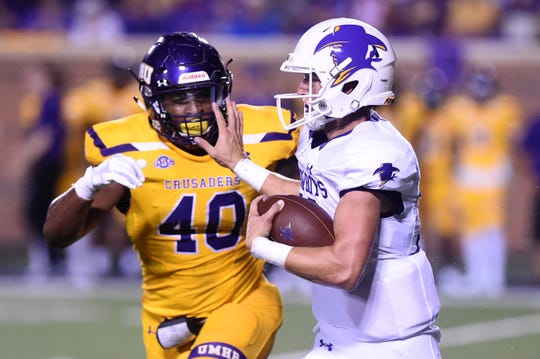 Hardin-Simmons quarterback Ty Hooper (12) braces for a hit from UMHB's De Jackson (40) at Crusader Stadium in Belton on Saturday, Oct. 6, 2018.