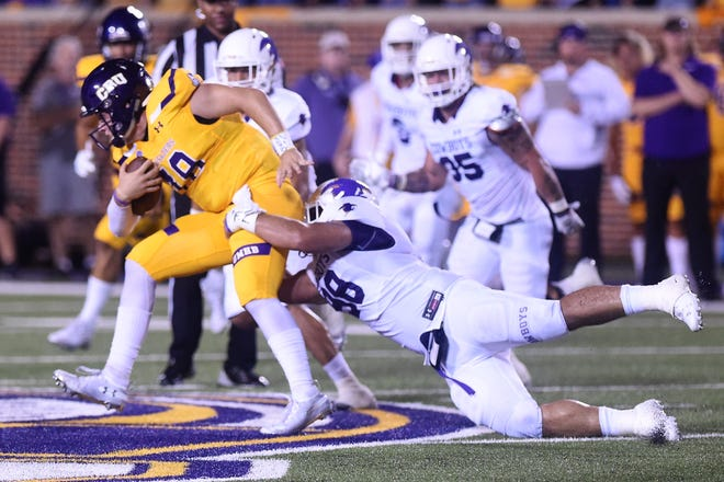Hardin-Simmons defensive lineman Kyle Zavala (98) wraps up UMHB quarterback Jase Hammack (18) at Crusader Stadium in Belton in an American Southwest Conference game. The Cru won 26-0, then eliminated the Cowboys from the Division III playoffs in the first round.